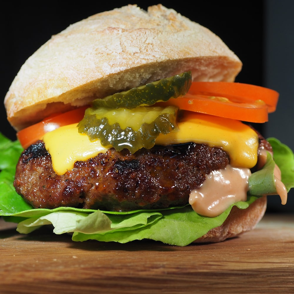 Big cheese hamburger with gherkins and tomatoes (Brief history of the Hamburger)