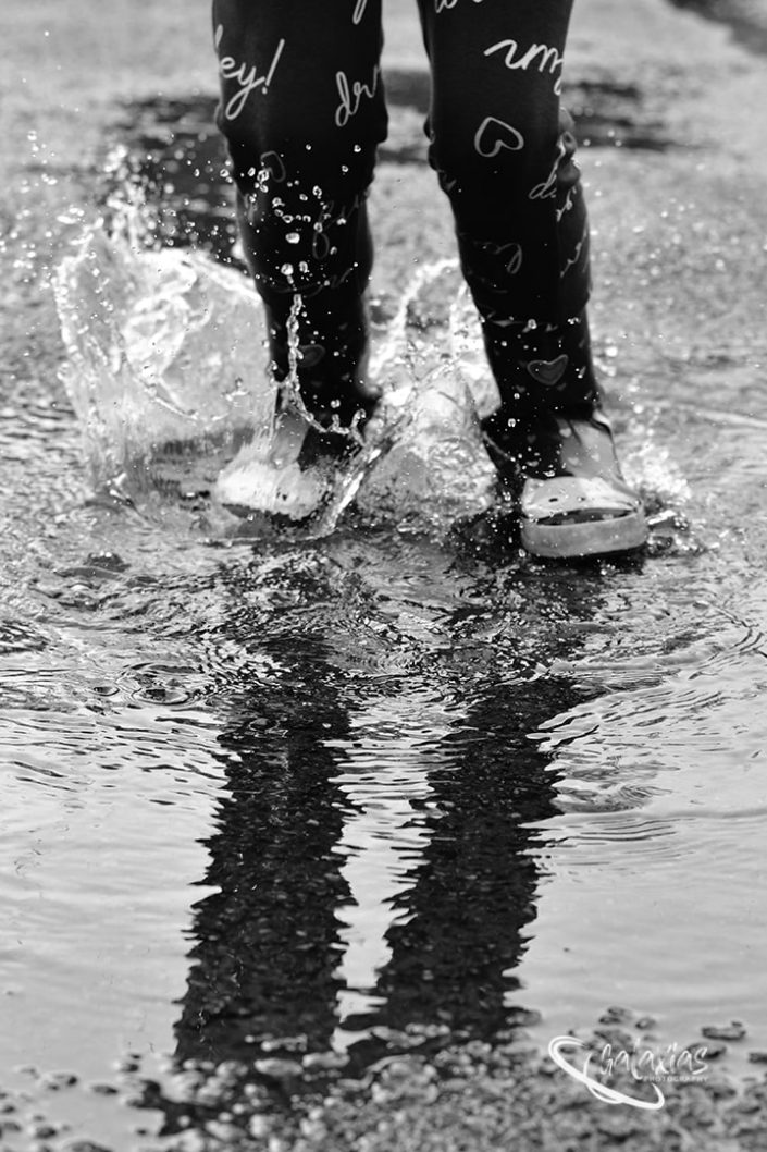 Black and White image of a child jumping in a puddle of water